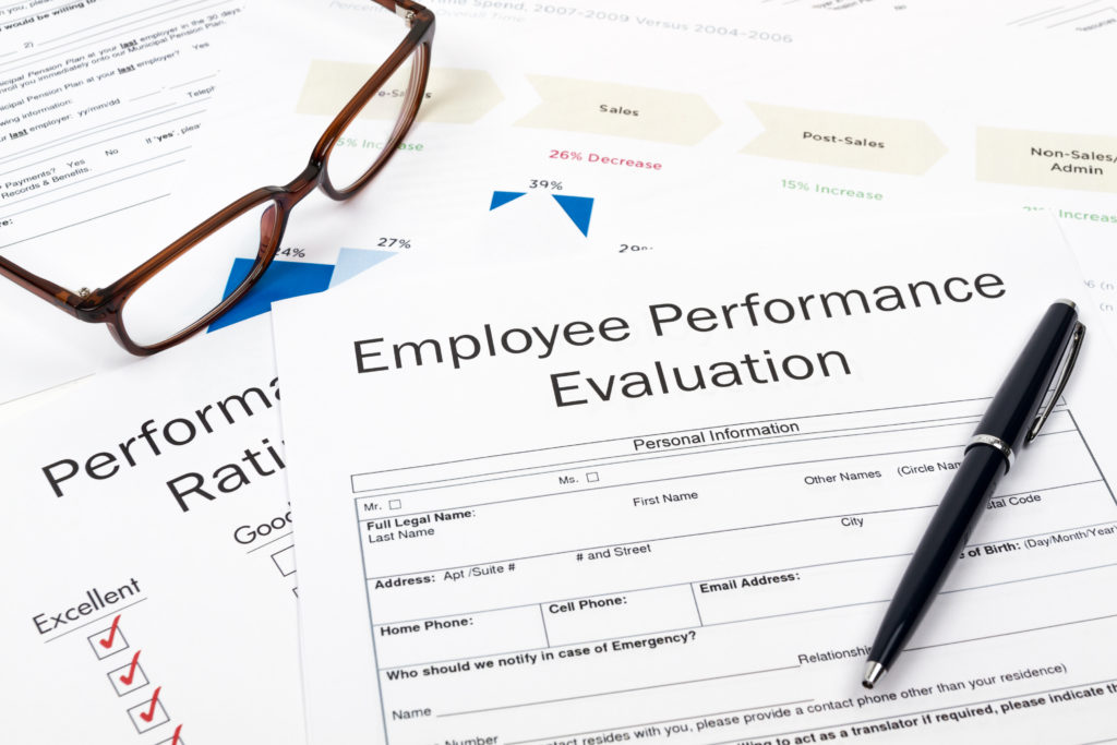 Hiring an employee? Glasses and Pen on Employee Performance Evaluation Sheets.