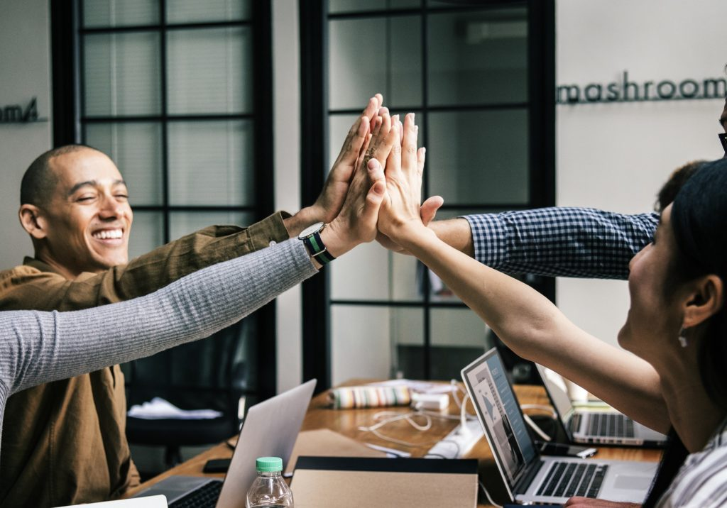Hiring an Employee? Group of multicultural individuals high fiving one another