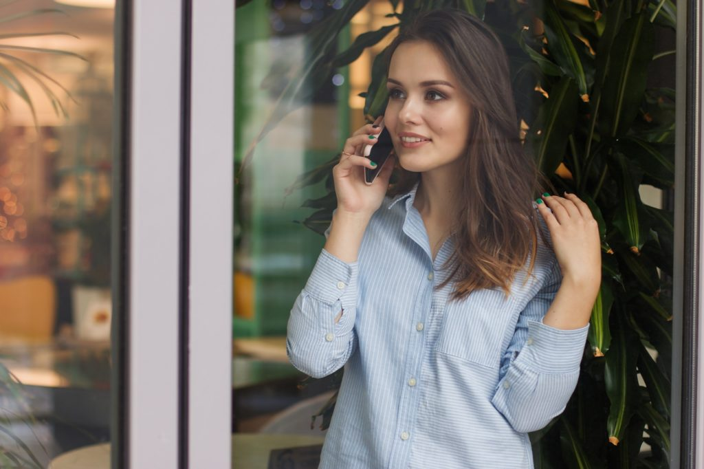Young woman with striped shirt talking on cellphone and smiling
