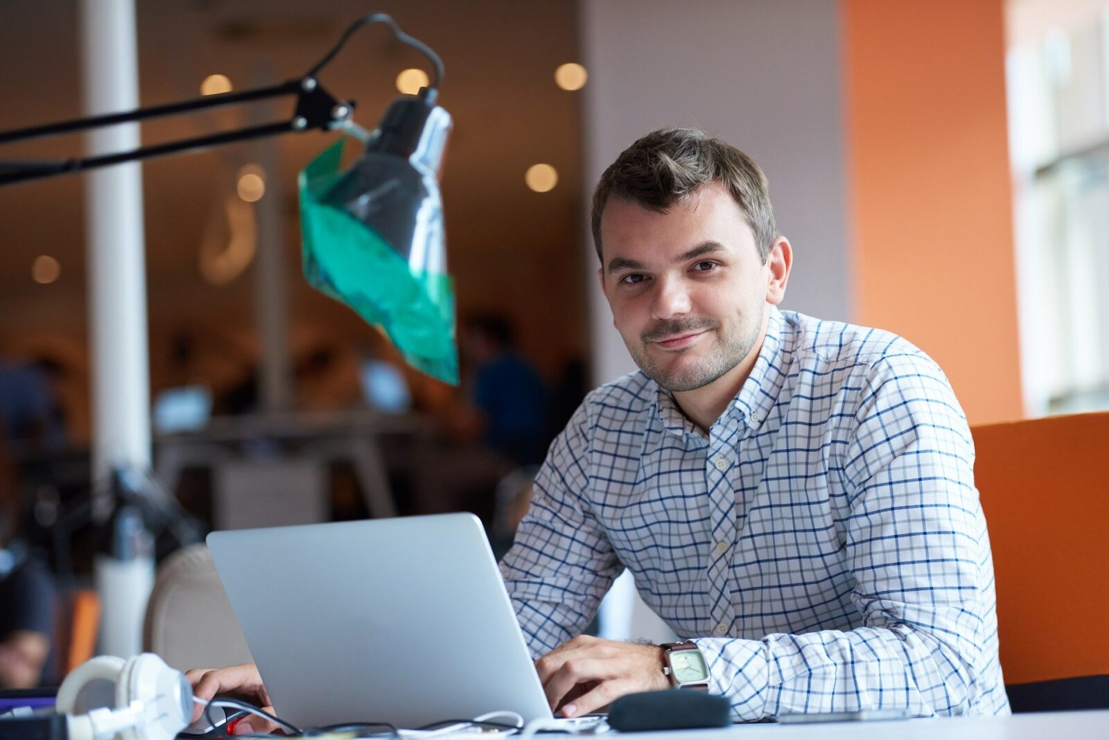 Office Manager sitting at desk in front of laptop smiling