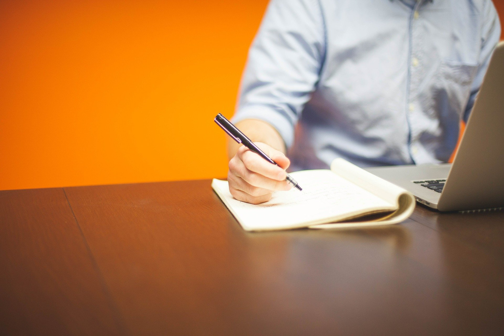 Procurement Director writing on paper in front of laptop
